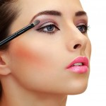 Eyes makeup. Brush applying eye shadows on beauty woman face.